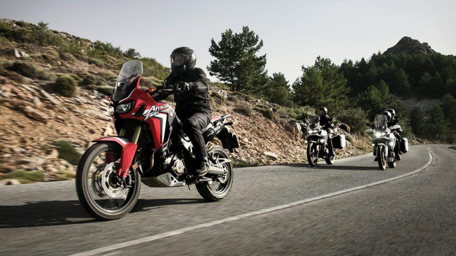 Tri motocykle Africa Twin prechádzajú zákrutou na ceste