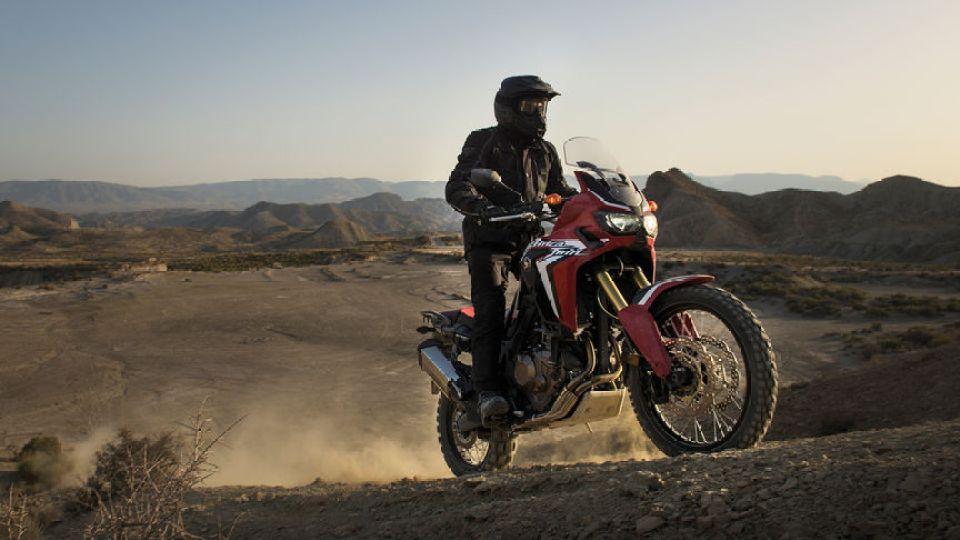 Jazdec stúpajúci svahom na motocykli Africa Twin