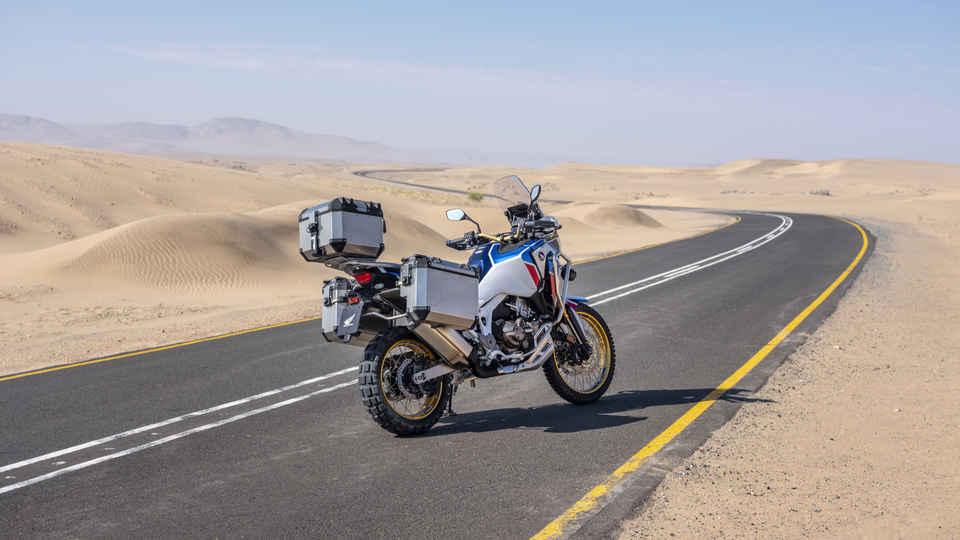 Trojštvrťový záber zhora z ľavej strany na model Honda Africa Twin Adventure Sports pri jazde po ceste v púšti