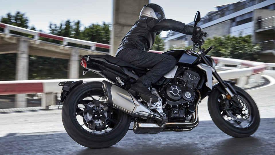 Predný trojštvrťový pohľad na motocykel Honda Neo Sports Café CB1000R so skladom vpozadí.