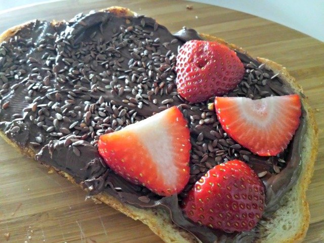 Layer the ingredients for your sweet protein sandwich: first Nutella, then flax seeds, strawberries, and finally apple slices
