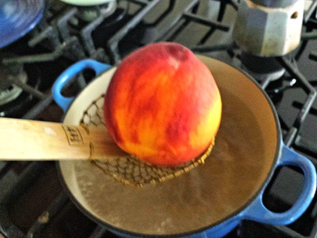 Lower peach carefully into boiling water
