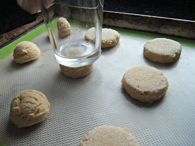 Use a glass to flatten the cookies
