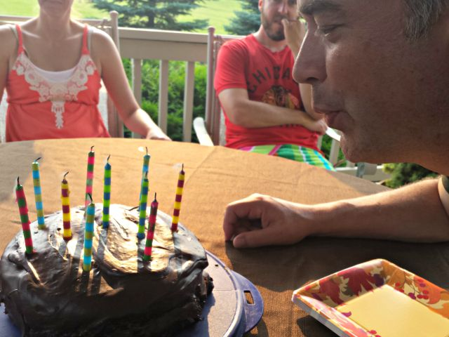 Blowing out candles of homemade strawberry cake