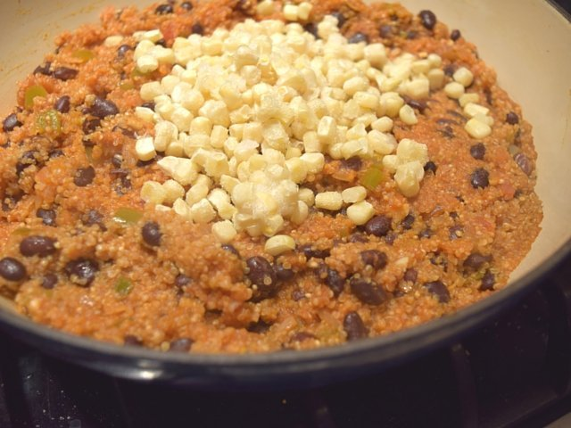 Add frozen corn to cooked quinoa and stir