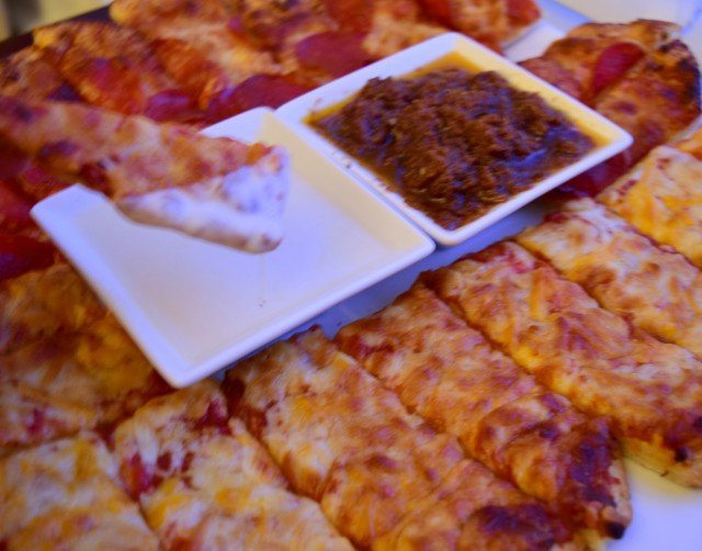 Dipping pizza in creamy garlic pizza dipping sauces