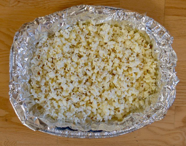 Add popcorn to foil lined baking dish