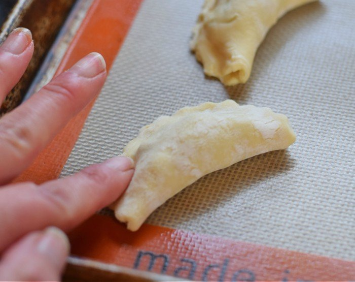 Gently press down on the edges of your empanadas to start a seal