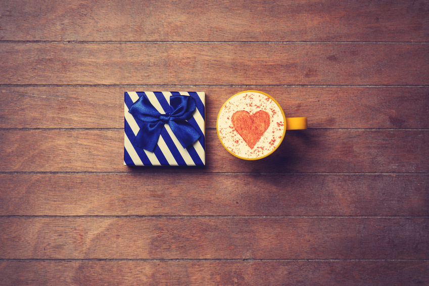 Cup of Cappuccino with heart shape symbol and gift box on wooden background