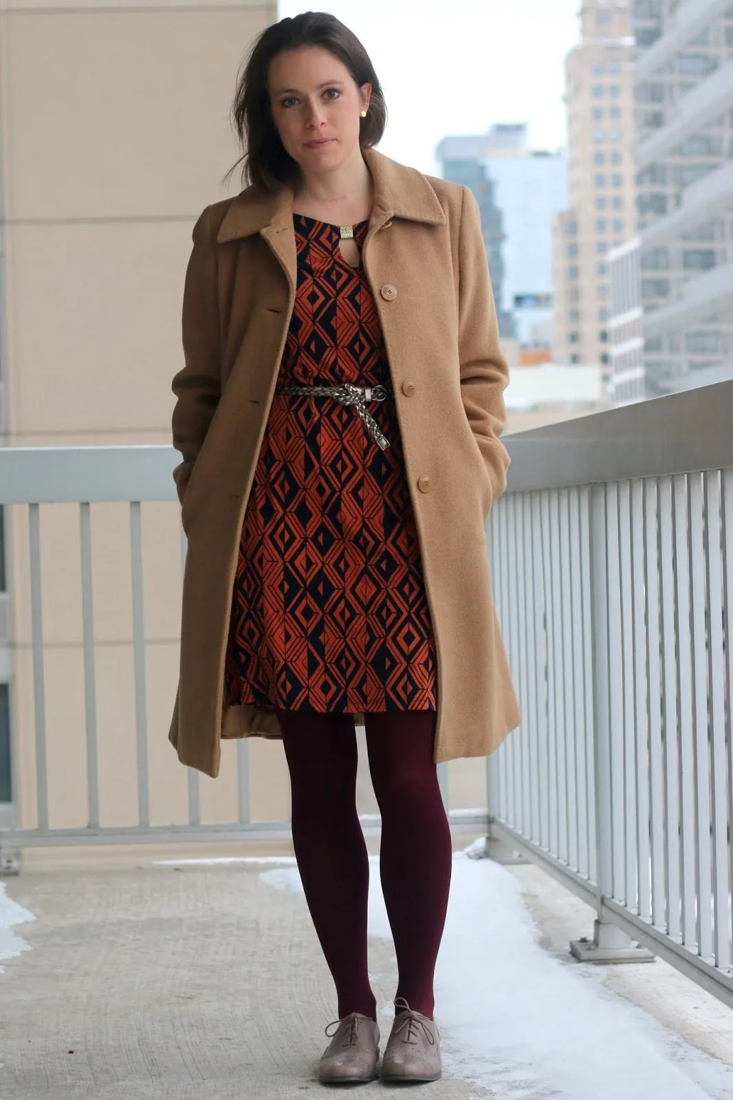 FashionablyEmployed.com | Orange and Navy geometric pattern dress, burgundy tights, gray belt and oxfords, camel winter coat | wear to work outfit, office style | versatile wardrobe workhorses