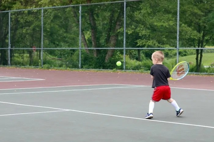 little boy hitting tennis ball on tennis court