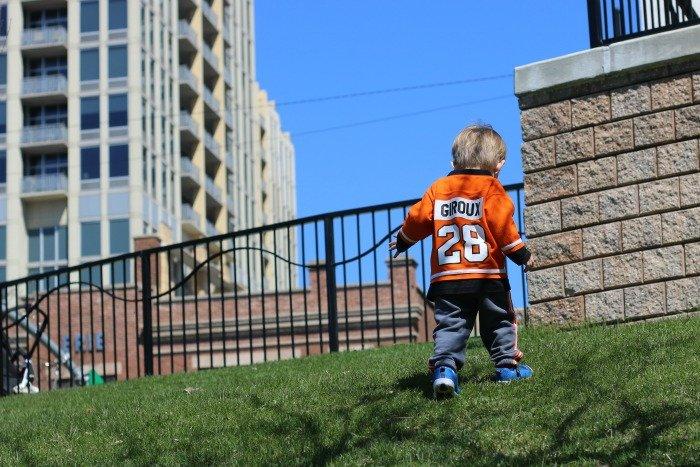 little boy walking up a hill near a playground