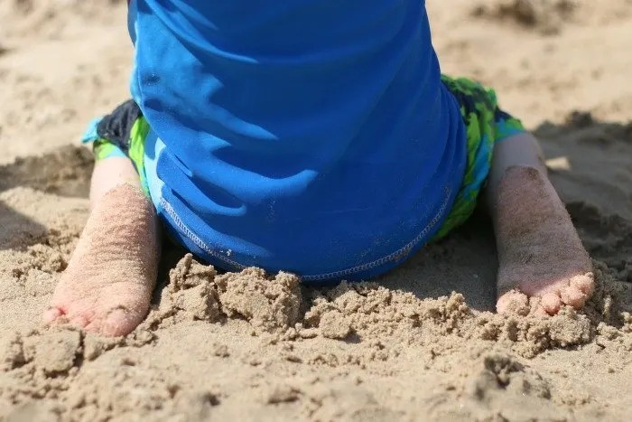 little boys feet sitting in the sand