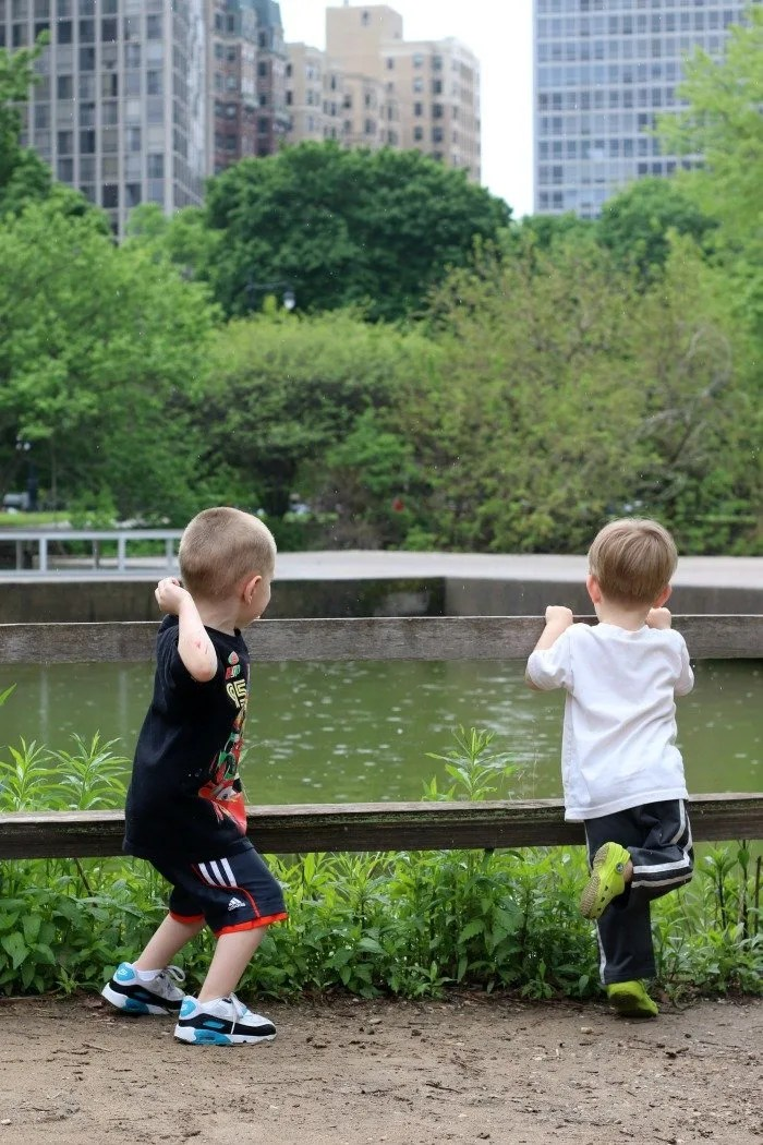 two boys throwing rocks into a pond