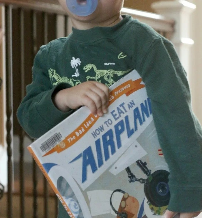 little-boy-holding-a-book-about-airplanes