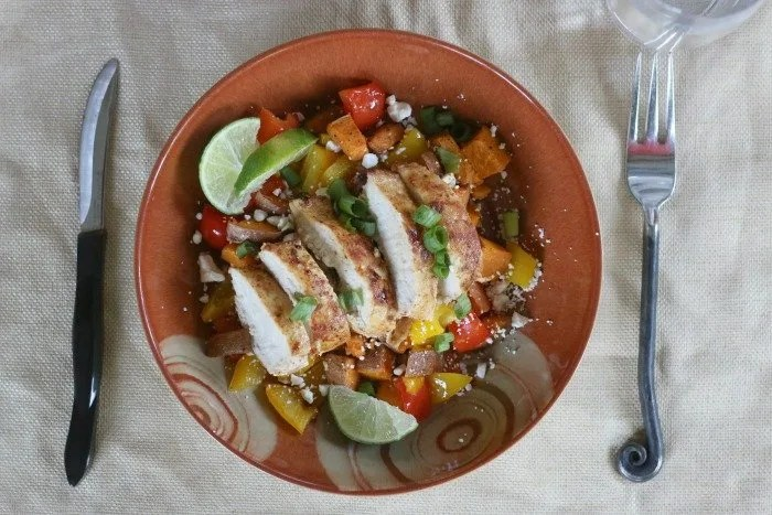 southwestern spiced chicken with peppers sweet potatos and lime wedges in a bowl