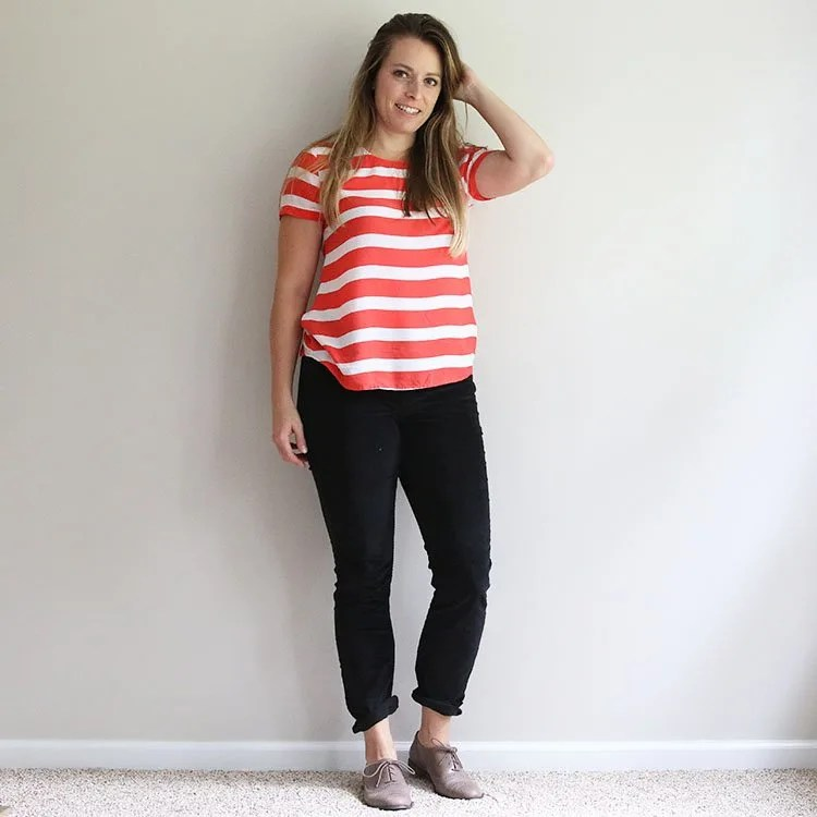 woman in orange and white striped shirt with black corduroy pants