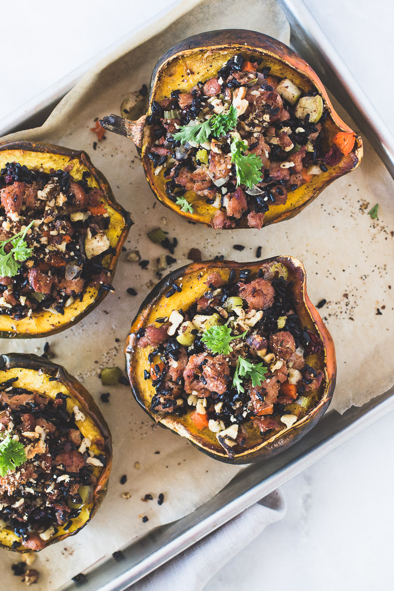 Roasted Acorn Squash Stuffed with Cranberry Chicken Apple Sausage and Forbidden Rice | A warm and comforting fall recipe that features acorn squash stuffed with a flavorful and hearty cranberry chicken apple sausage and black forbidden rice filling. This dish is extremely simple to prepare yet it will wow anyone lucky enough to be invited to the table. Click to get the recipe! | Honestly Nourished | www.honestlynourished.com