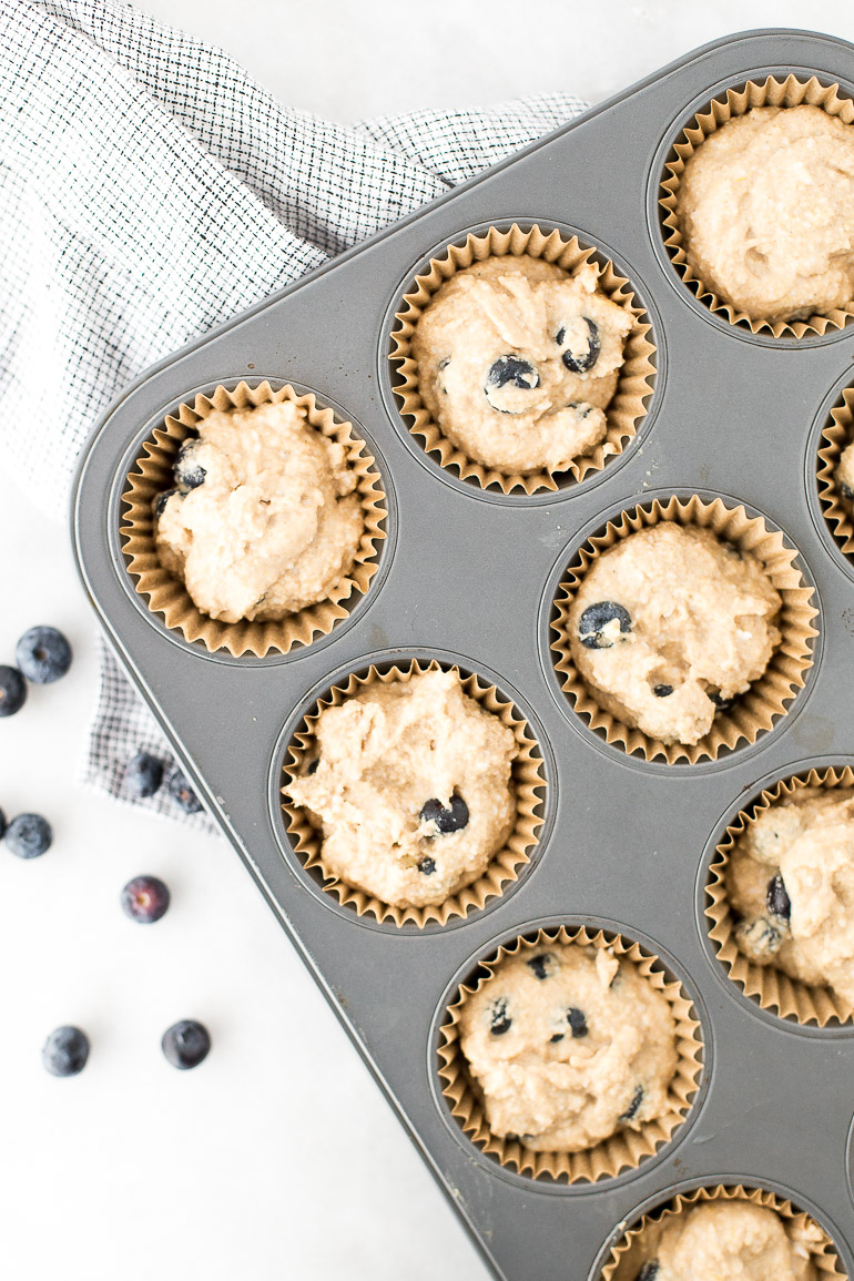 Bursting with fresh blueberries and topped with an indulgent coconut butter crumb topping and coconut butter drizzle, these muffins will simplify and elevate breakfast all week! | via Honestly Nourished