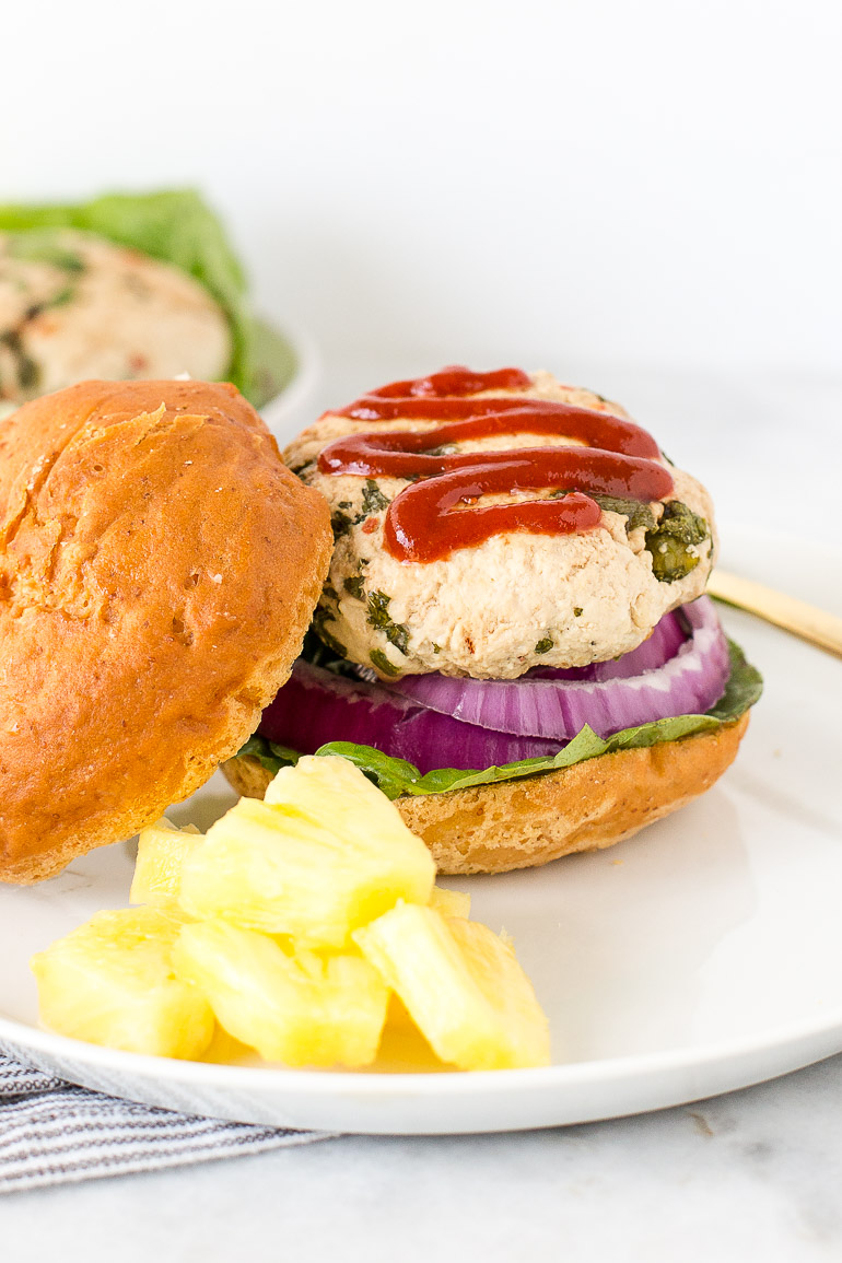 Elevate your next summer barbecue or grill out with this Thai-spiced pineapple turkey burger! It's a healthy twist on a summertime staple that will offer your taste buds a much-needed vacation from the typical ketchup- and mustard-laden fare. | paleo + gluten free + dairy free | Honestly Nourished