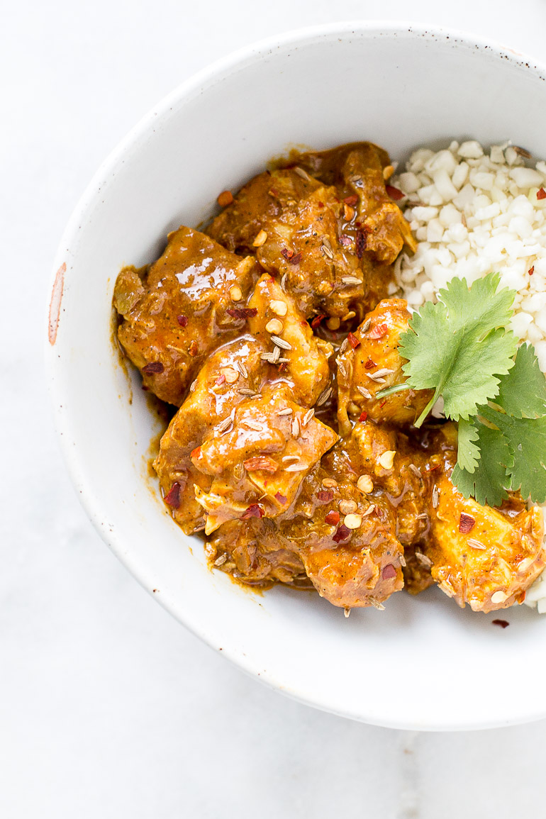 A lightened up, dairy-free recipe for one of India's beloved dishes, this slow cooker/crock pot recipe uses coconut milk and oil in lieu of butter for a healthier, paleo-friendly, gluten-free meal. Just add cauliflower or regular rice and dinner is done! | via Honestly Nourished
