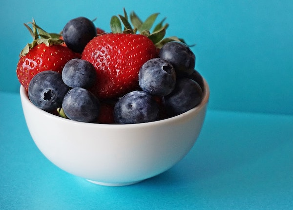 blueberries and strawberries in white ceramic bowl