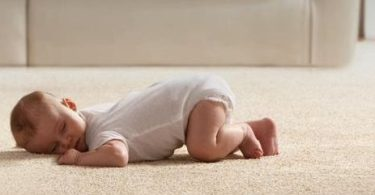 Baby infant lays on carpet tummy time