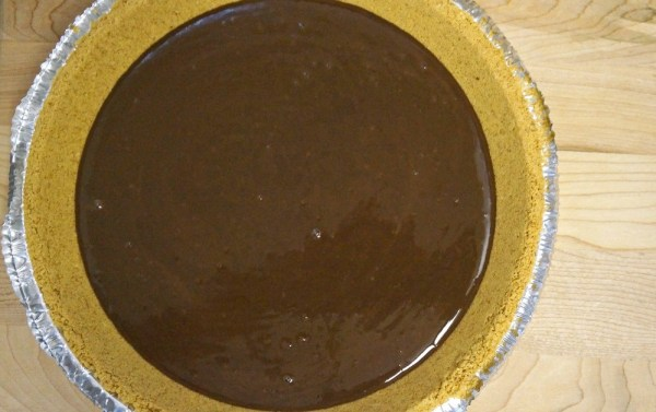 Pour melted chocolate into graham cracker pie crust
