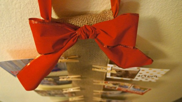 DIY red bow decoration on a wall Christmas card holder