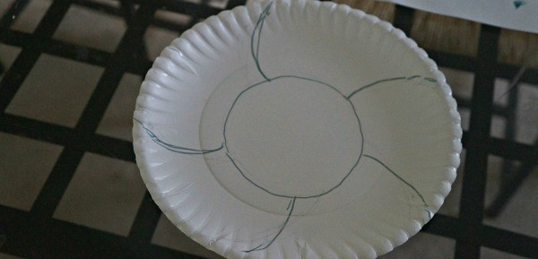Making a paper plate Easter basket craft, prep the plate