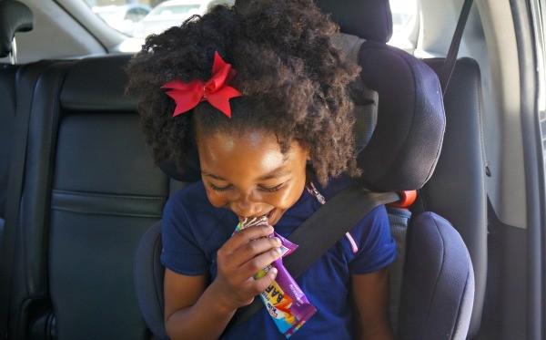Kid girl eating CLIF Kid Zbar fruits and veggies bar