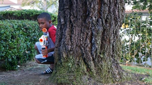 Boy hiding in backyard NERF blaster battle