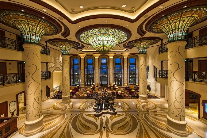 The sweeping, three-story lobby of Shanghai Disneyland Hotel envelops guests in the Art Nouveau-inspired décor as soon as they step inside. A large, glass peony blossom at the entrance is one of the many special Chinese features of the hotel. it's one of the largest sculpted, solid glass flowers in all of China. (Matt Stroshane, photographer)