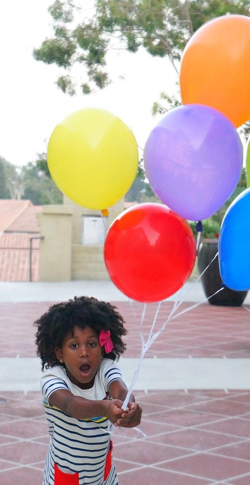 Beautiful little natural brown girl on her first day of school with rainbow balloons