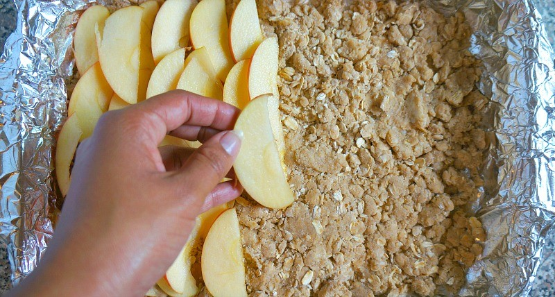 Making apple cinnamon oatmeal bars, layer apples on top of the oat mixture