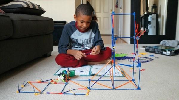 Holiday STEM gifts, boy builds the K'NEX Wild Whiplash Roller Coaster