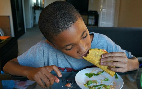 Kid eating tacos on National Crunchy Taco Day