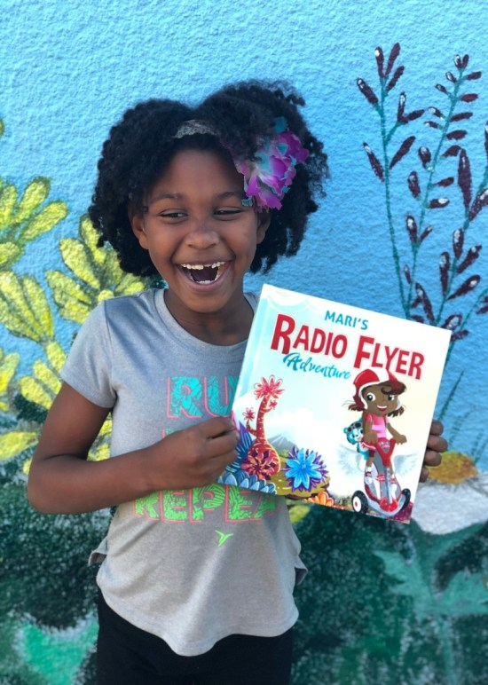 Little girl with personalized I See Me Radio Flyer book