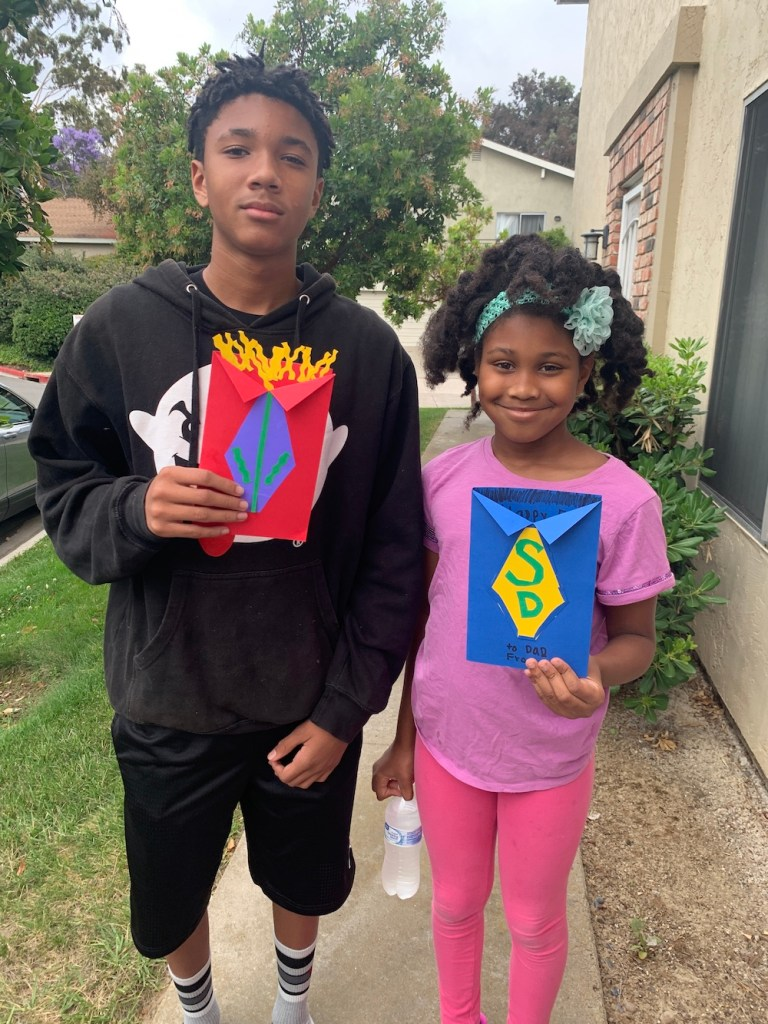 Kids with their homemade Father's Day shirt and tie cards