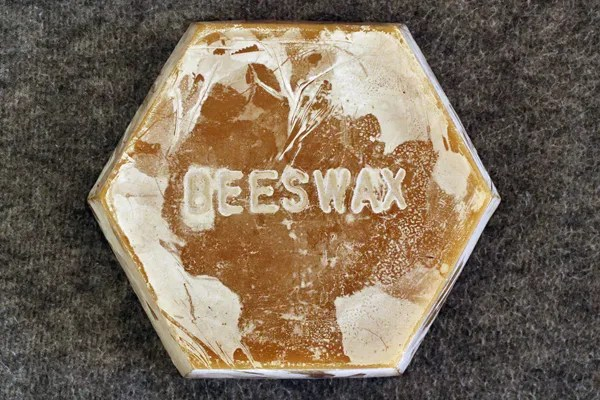 This cake of rendered beeswax is several years old and is coated with wax bloom. Note how the bloom enhances the lettering.