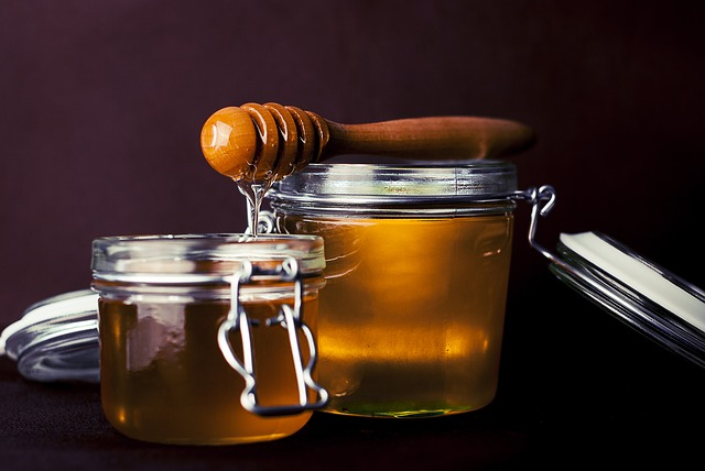 A honey dipper dripping into a pot of honey.