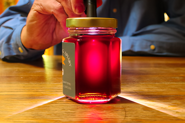 Lit by a high-intensity LED flashlight, the honey glows in various shades of red, purple, and pink.