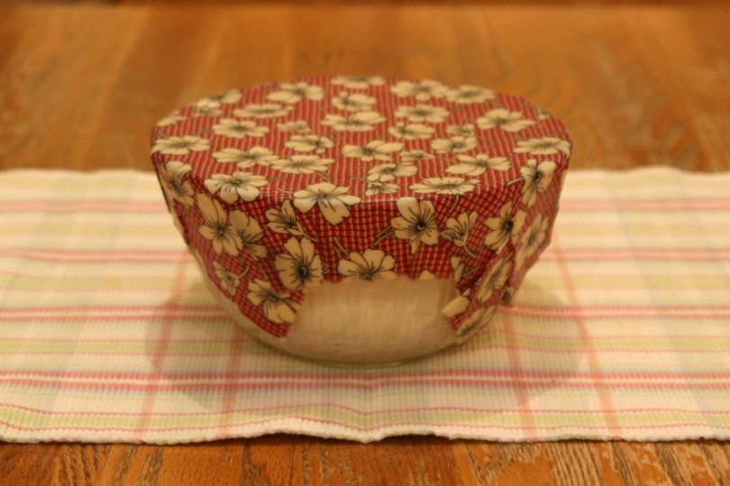Pizza dough rising: This pizza dough is rising under a beeswax wrap. Holding your hands against the wrap-covered container for a few moments will help make a tight seal.