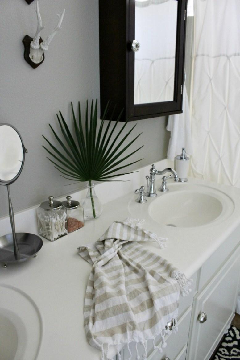 Builder's grade master bathroom makeover on a budget, add wood feet to a bathroom vanity, fix swollen MDF cabinet doors, fan leaf palm, patterned tile rug