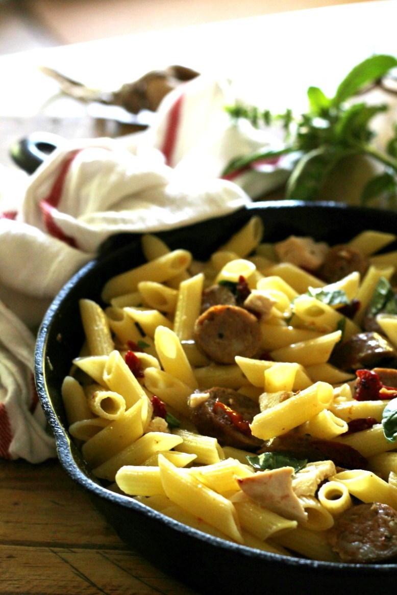 Gluten free penne pasta with sun dried tomatoes, sausage and fresh basil