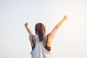 Eine Frau ist glücklich durch Ansporn Glaubenssätze