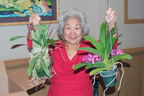 President Ruth Chun holds up plants donated by David Bealer.  The plants were given away as lucky number prizes.