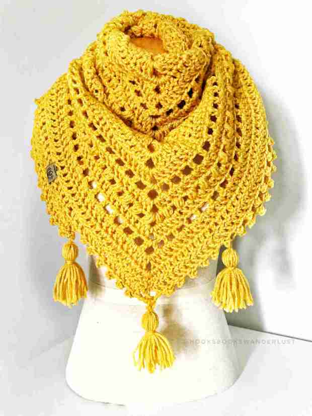 A mustard colored chunky version of the Autumn Walks Triangle Scarf is wrapped around the neck of a mannequin.