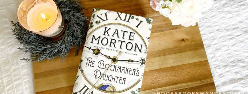 A hardcover copy of The Clockmaker's Daughter sits on a wood board laying on a white background. A lit cream-colored candle set in a wreath of fir tree greenery sits to the left of the book and a cream and peach bouquet of silk flowers lays to the right.