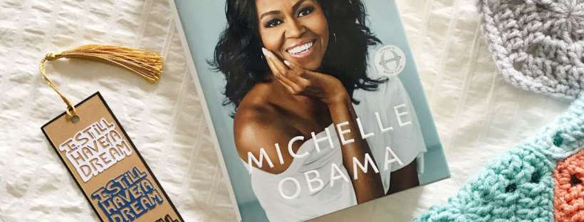 """A hardcover copy of """"Becoming"""" by Michelle Obama lays on a white bedspread next to a handmade paper bookmark with the words """"I still have a dream"""" on it next to a brightly colored crochet blanket in coral, gray and teal."""